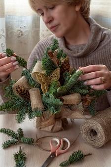 Una donna che fa il mazzo invernale di rami di abete rosso, coni e tela