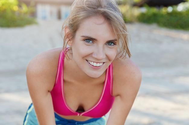 Una donna che fa jogging soddisfatta riprende fiato dopo una corsa mattutina attiva, felice di avere una motivazione sportiva, trascorre il tempo libero all'aria aperta vestita con reggiseno sportivo. allenarsi all'aperto. persone e concetto di stile di vita