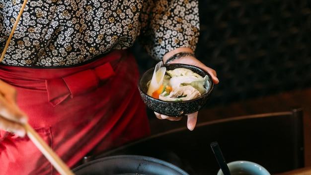 Una donna che indossa il kimono tiene sukiyaki bollito in una ciotola.