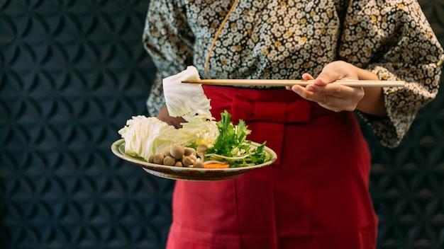 Una donna che indossa kimono tenendo cavolo sopra set di verdure sukiyaki.