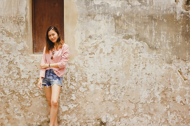 Una donna che indossa una camicia rosa appoggiata a un vecchio muro.