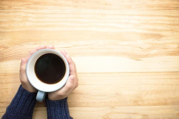 Una donna che indossa una maglia blu con una tazza di caffè con le mani.