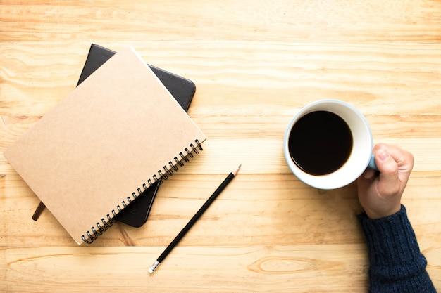 Una donna che indossa una maglia blu con una tazza di caffè e due libri