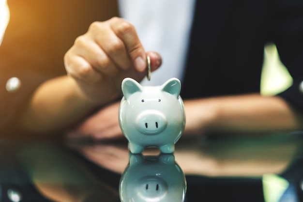Una donna che mette le monete nel salvadanaio per il concetto di risparmio di denaro