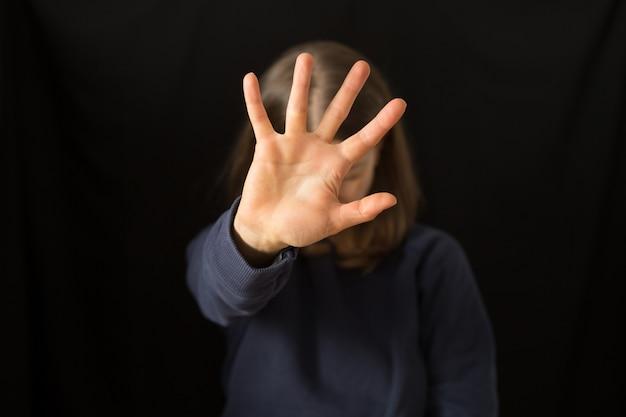 Una donna che piange si copre il viso con la mano. la violenza domestica.