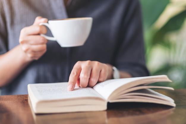 Una donna che punta e legge un libro mentre beve il caffè sul tavolo di legno
