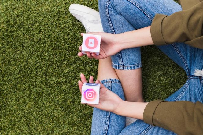 Una donna che si siede sull'erba verde che tiene icone social media nelle mani