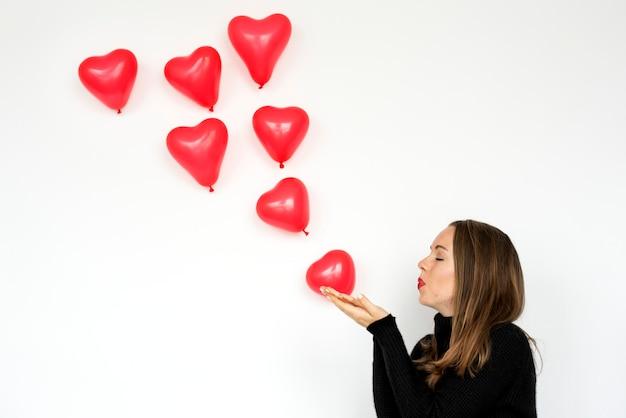 Una donna che soffia palloncini cuore