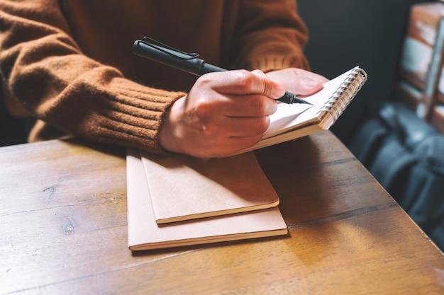 Una donna che tiene e scrivere sul taccuino in bianco con la penna stilografica sulla tavola di legno