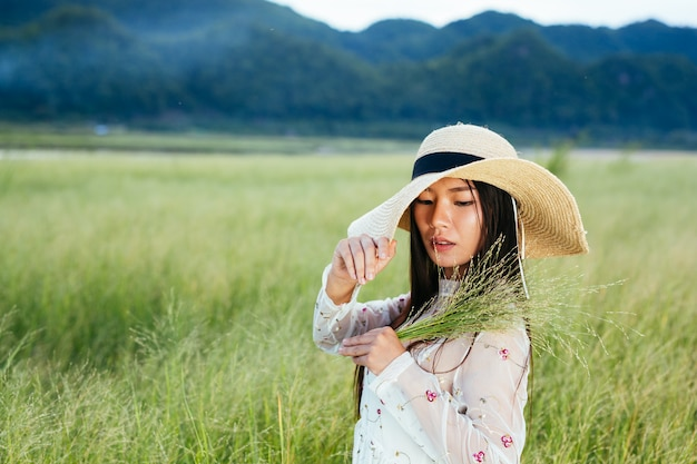 Una donna che tiene in mano un'erba su un bellissimo campo in erba con una montagna.