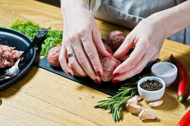 Una donna chef prepara polpette svedesi da carne macinata cruda.