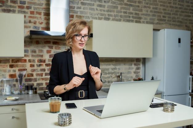 Una donna con gli occhiali lavora a distanza su un laptop nella sua cucina. una ragazza bionda che gesticola discute con i suoi colleghi su un briefing aziendale online a casa. una signora che tiene lezioni su un webinar.