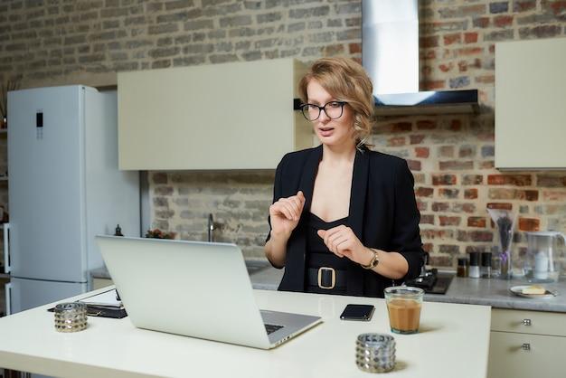 Una donna con gli occhiali lavora a distanza su un laptop nella sua cucina. una ragazza bionda che gesticola discute con i suoi colleghi su un briefing aziendale online a casa.