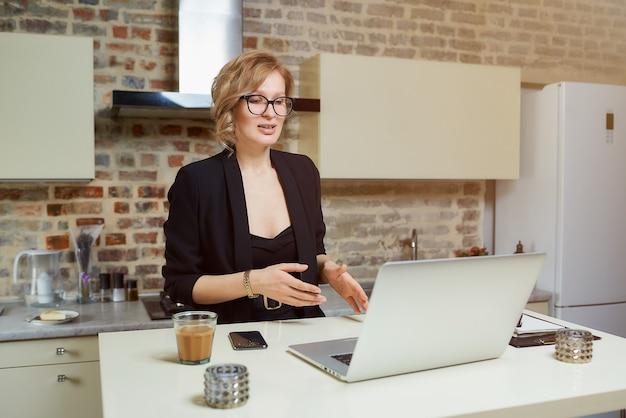 Una donna con gli occhiali lavora a distanza su un laptop nella sua cucina. una ragazza bionda che gesticola discute con i suoi soci in una videoconferenza a casa.