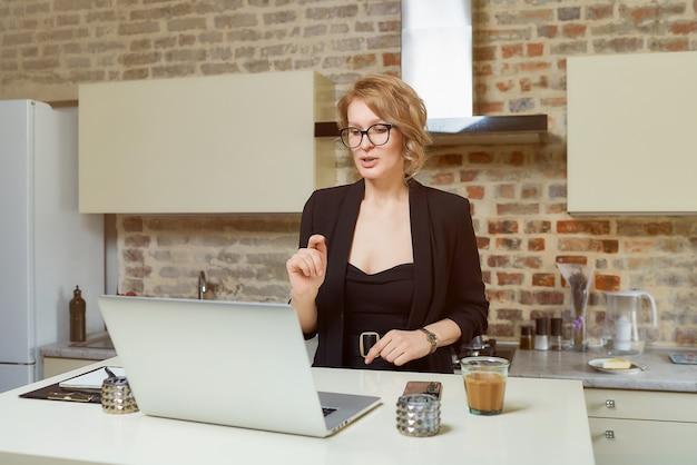 Una donna con gli occhiali lavora a distanza su un laptop nella sua cucina. una ragazza bionda con le parentesi graffe che gesticola discute con i suoi colleghi in una videoconferenza a casa.