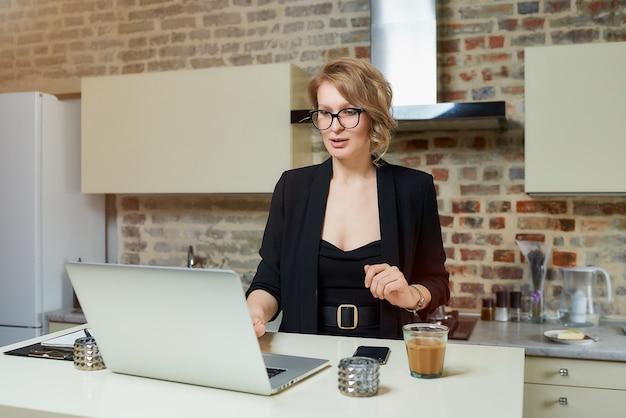 Una donna con gli occhiali lavora a distanza su un laptop nella sua cucina. una ragazza che gesticola discute con i suoi colleghi su un briefing aziendale online a casa.