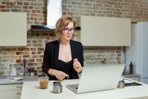 Una donna con gli occhiali lavora a distanza su un laptop nella sua cucina. una ragazza discute con i suoi colleghi su un briefing aziendale online a casa.