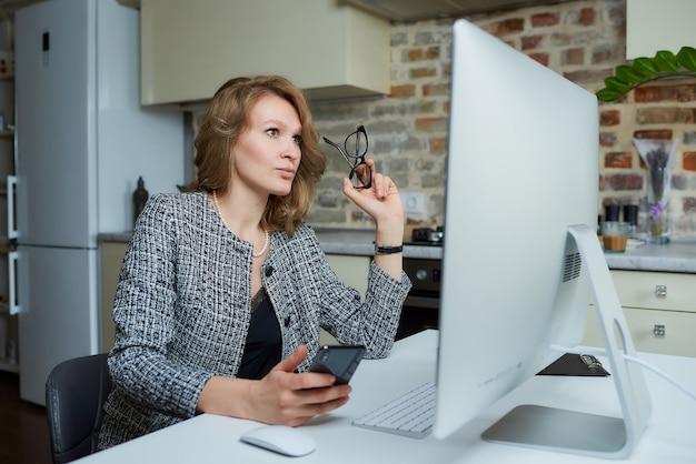 Una donna con gli occhiali lavora da remoto su un computer desktop nel suo studio. una signora usa un telefono durante una videoconferenza a casa. una professoressa che ascolta le risposte degli studenti durante una lezione online.