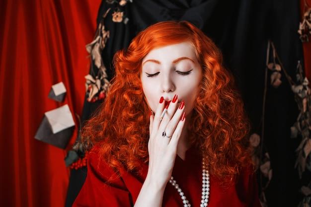 Una donna con i capelli rossi in un abito rosso con una sigaretta in bocca. ragazza dai capelli rossi con la pelle pallida e gli occhi azzurri con un aspetto insolito brillante con perline intorno al collo. immagine noir