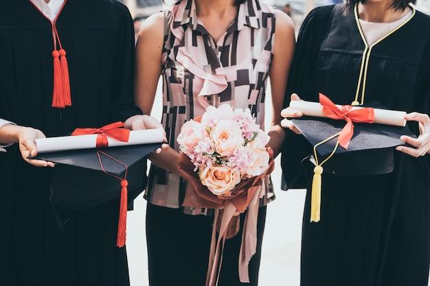 Una donna con il mazzo si congratula per la sua famiglia il giorno della laurea, concetto di successo