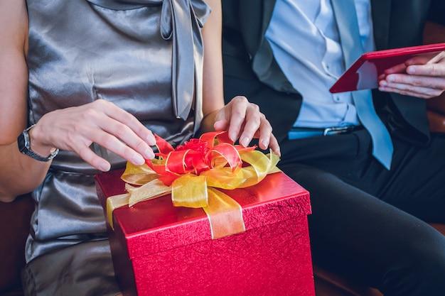 Una donna con in mano la confezione regalo rossa.