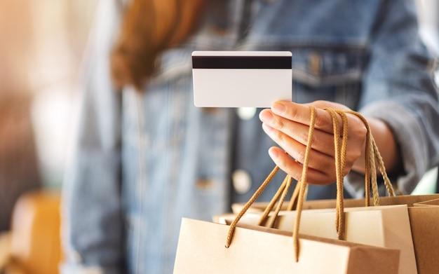 Una donna con le borse della spesa in possesso e utilizzando una carta di credito per l'acquisto
