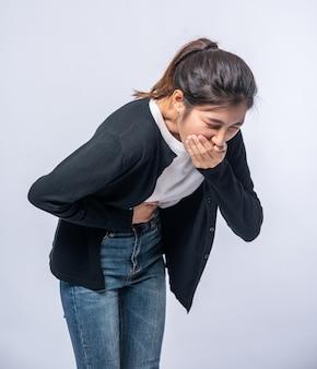 Una donna con mal di stomaco si mette le mani sullo stomaco e si copre la bocca.