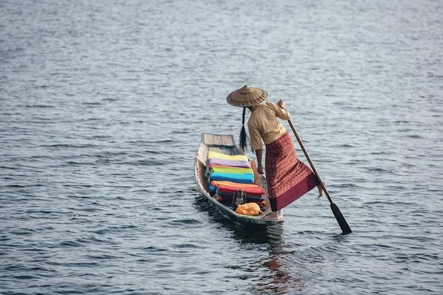 Una donna con tessuti di loto colorati artigianali sulla sua barca nel villaggio di dain khone, sul lago inle, myanmar.