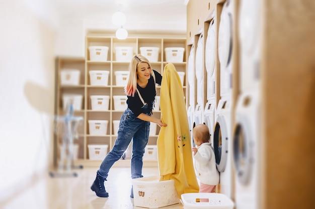 Una donna con un bambino mette le lenzuola nel bucato
