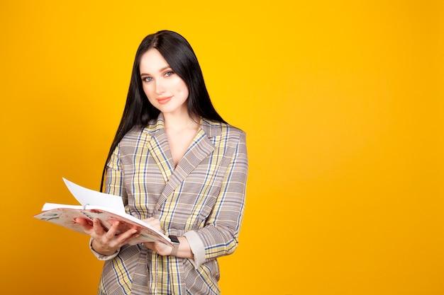 Una donna con un blocco note su un semplice sfondo giallo. il concetto di imprenditrice o pianificazione, lavoro femminile.