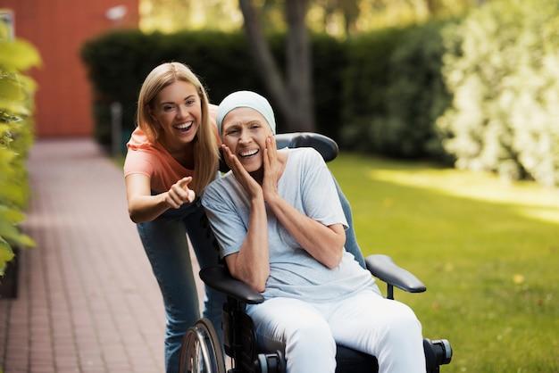 Una donna con un cancro è seduta su una sedia a rotelle