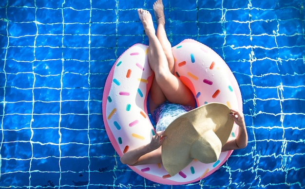 Una donna con un cappello si rilassa su un cerchio gonfiabile in piscina.