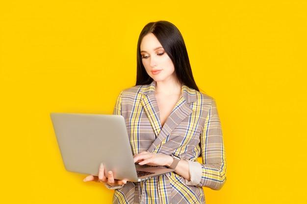 Una donna con un computer portatile in mano, su un muro giallo brillante, con spazio di copia. il concetto di lavoro a distanza e lavoro su internet, donna d'affari.