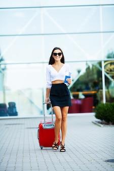 Una donna con un passaporto e una valigia rossa vicino all'aeroporto sta andando in viaggio