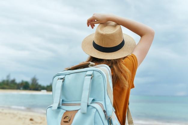 Una donna con uno zaino blu in un abito giallo e cappello cammina lungo l'oceano lungo la sabbia con le palme