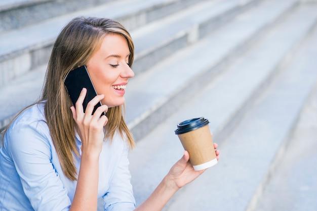 Una donna d'affari che controlla il email tramite il telefono mobile e tiene una tazza di caffè contro la scena urbana.