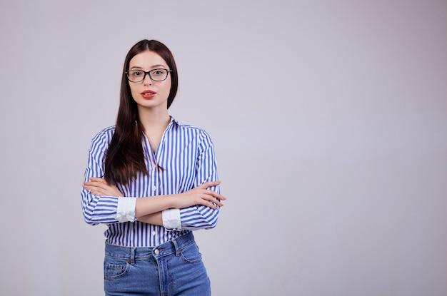 Una donna d'affari giovane piacevole è in piedi nel, guardando dritto. copia spazio