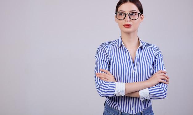 Una donna d'affari piuttosto calma e piacevole con gli occhiali traslucidi è in piedi e guarda lateralmente