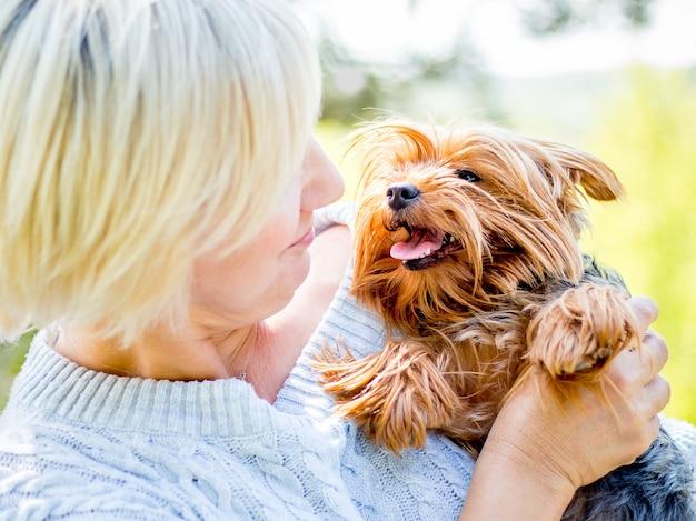 Una donna dai capelli chiari sta giocando con un giovane cane di razza yorkshire terrier
