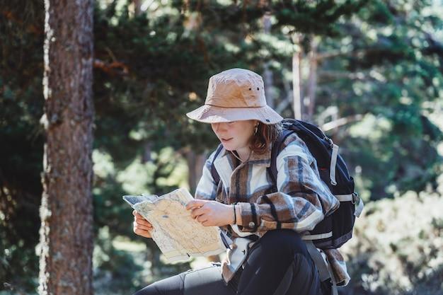 Una donna dai capelli rossi con cappello e zaino, visita di una foresta guardando una mappa seduta su un tronco d'albero