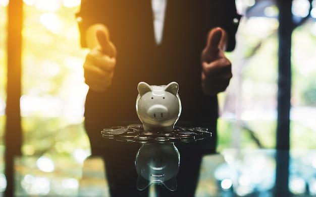 Una donna di affari che fa e che mostra i pollici aumenta il segno della mano con il porcellino salvadanaio e le monete sulla tavola per il concetto dei soldi di risparmio