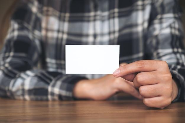 Una donna di affari che tiene e che mostra un biglietto da visita vuoto