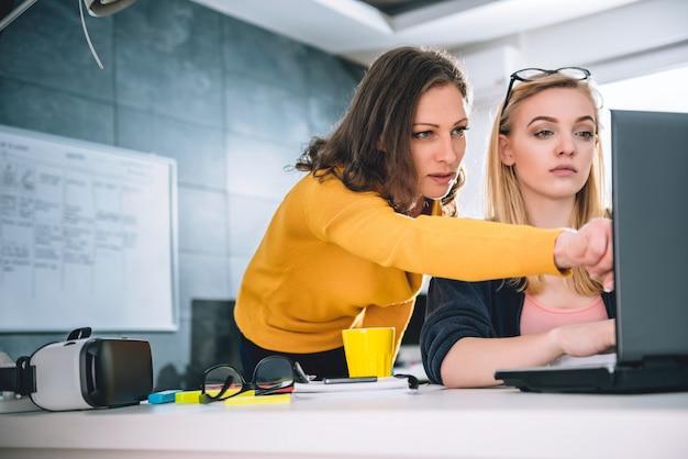 Una donna di due affari che lavora all'ufficio e che per mezzo del computer portatile