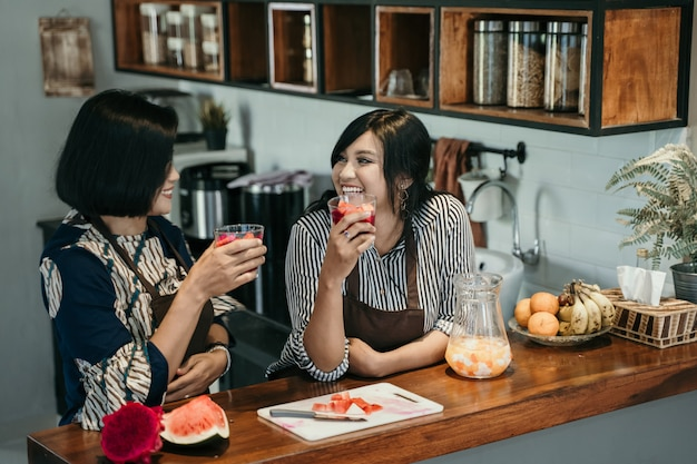 Una donna di due asiatici gode della bevanda dolce nella cucina