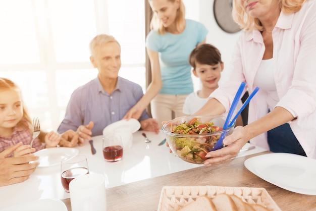 Una donna di mezza età serve un'insalata per la sua famiglia.