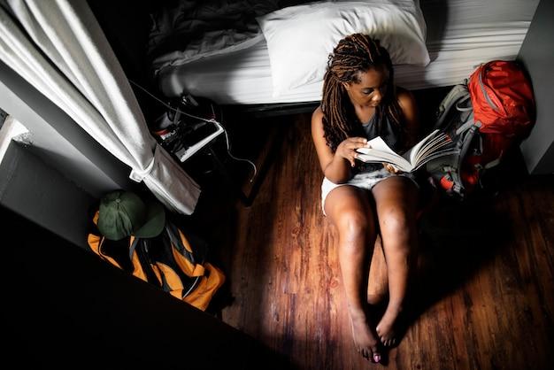 Una donna di origine africana che si siede sul pavimento di legno leggendo un libro
