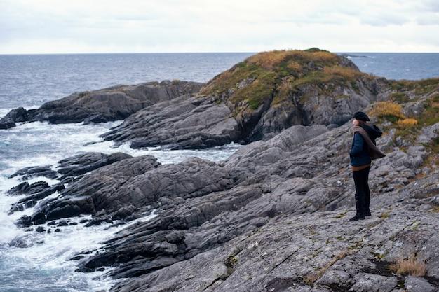 Una donna è in piedi sulla roccia di montagna a lofoten, norvegia