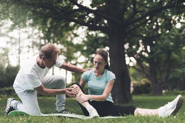 Una donna è seduta su un tappeto e si tiene su una gamba ferita.