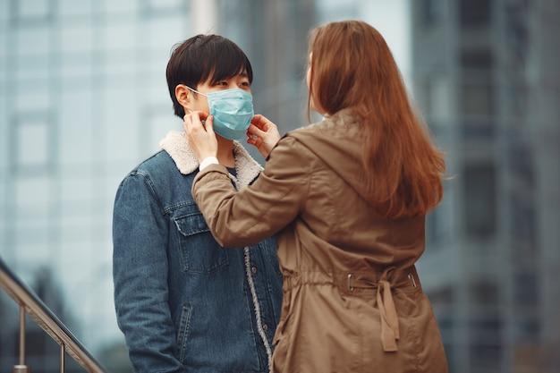 Una donna e un uomo cinese indossano maschere protettive