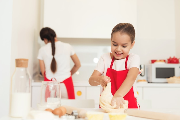 Una donna e una ragazza in grembiuli rossi cuociono i biscotti